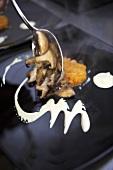 Spooning sautéd mushrooms onto a plate