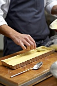 Spreading cream in a tart tin lined with pastry