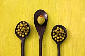 Stuffed olive and green peppercorns on three wooden spoons