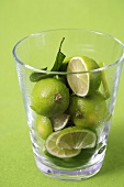 Whole and sliced limes in a glass