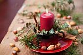 Emailtasse mit Kerze, Efeu, Kiefernzweigen und Zimtstangen