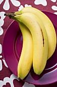 Three bananas on purple plate