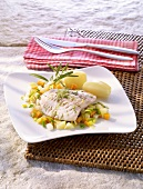 Redfish cooked in foil on vegetables with potatoes