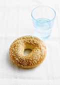 Sesame bagel with a glass of water