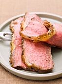 Slices of roast beef on plate with meat fork