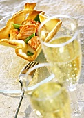 Salmon in puff pastry basket, glasses of sparkling wine