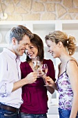 People clinking glasses of white wine