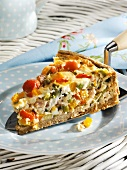 A piece of mixed vegetable tart on cake slice