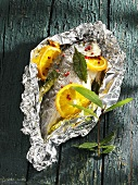 Sea bream with orange slices & bay leaves in aluminium foil