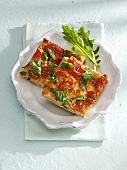 Two pieces of wholemeal pizza with tomatoes, mozzarella & rocket