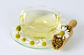 Chamomile tea in glass cup and saucer with flowers