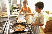 Two boys frying fish cakes