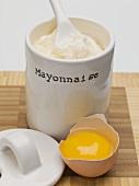 Mayonnaise in a pot, broken egg