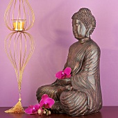 Buddha figure with orchids and candle in glass