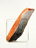 A slice of salmon with skin in a glass