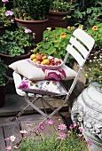 Eine Schale mit Tomaten und Pfirsichen auf einem Gartenstuhl