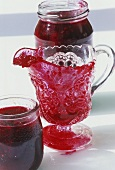 Putting apple and berry jam into jars