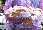 Frau trägt Etagere mit Cupcakes & Baisertörtchen