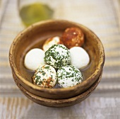 Soft cheese balls with herbs and spices in oil