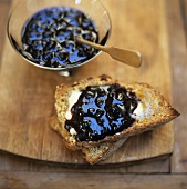 Blueberry jam on toasted bread and in small bowl