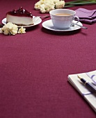 A cup of tea and cherry cheesecake