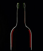 A bottle of red wine against a black background