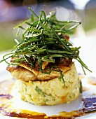 Fried fish fillets with chives on vegetable cake