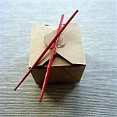 A noodle box with chopsticks