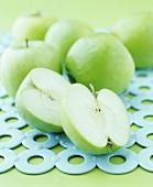 Grüne Äpfel, ganz und halbiert