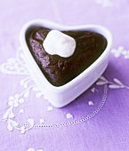 Chocolate pudding with cream in heart-shaped dish