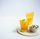 Orange drinks with ice cubes, bowl of pistachios beside them
