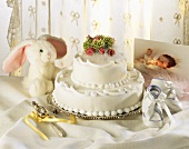 Two-tiered white cake with gifts for christening