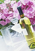 A bottle of white wine with hydrangeas in background