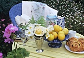 Flowers, yellow plums and raisin buns on garden table