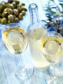 White retsina in glasses and bottle, olives behind