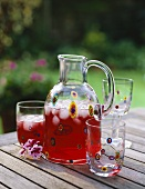 Carafe and glass of cranberry juice on a garden table