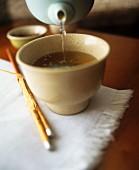 Pouring chai tea into a tea bowl