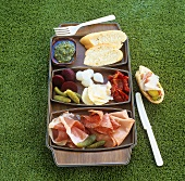 Cold cuts, pickled vegetables, pesto & baguette for picnic