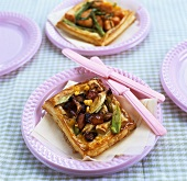 Puff pastry vegetable tartlet with pink plastic cutlery