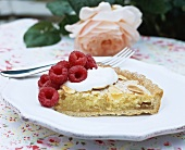 A piece of almond tart with raspberries and cream