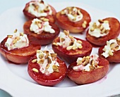 Baked peaches with raspberry sauce, cream and pine nuts