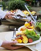 Teller mit Grillspiess, Maiskolben und Salat