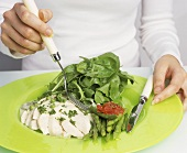 Woman eating halibut with spinach salad and asparagus