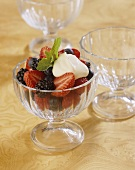 Fresh summer berries with crème fraîche in dessert glass