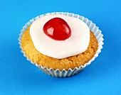 Iced cupcake with cherry on blue background
