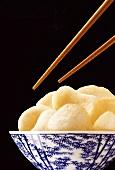 Chopsticks over a bowl of prawn crackers