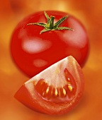 Tomato and wedge of tomato against red background