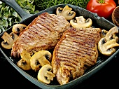 Two beef steaks with mushrooms in a grill pan