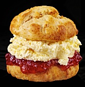 Scone with jam and cream against black background