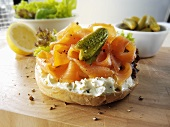 Bagel topped with cream cheese, smoked salmon and gherkin